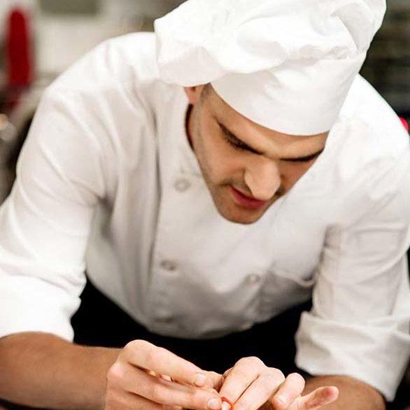 Male chef decorating salad of aubergine